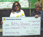 Patty Johnson being presented a check for $5,000 by WaMu Hillcrest branch manager for the Friday, August 24 Smile-Off